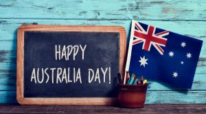 Blackboard with the words Happy Australia Day and a small Australian flag next to it