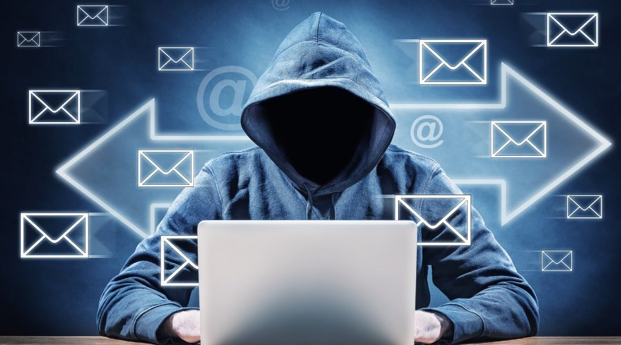 A hooded figure sitting in front of a laptop with emails icons floating around him