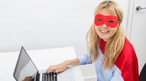 A woman dressed as a superhero sitting in front of a laptop